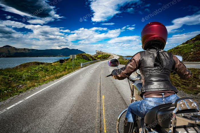 Biker girl rides a mountain road in Norway Atlantic Ocean Road.