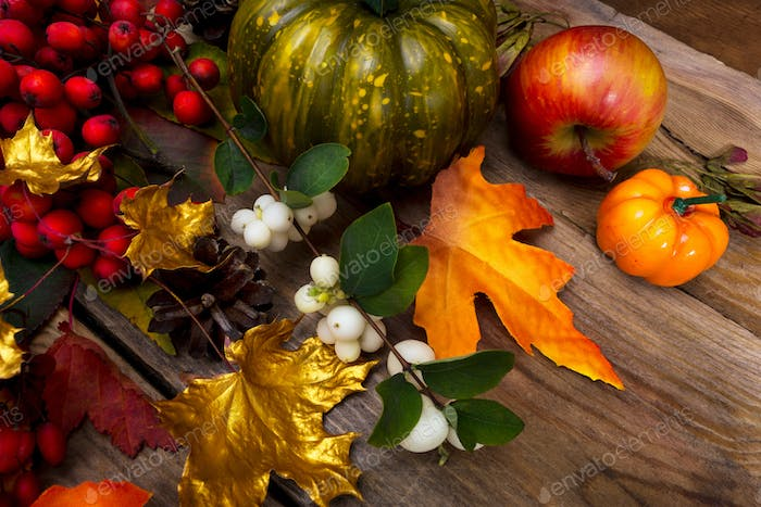 Fall background with rowan and white berries on the rustic woode