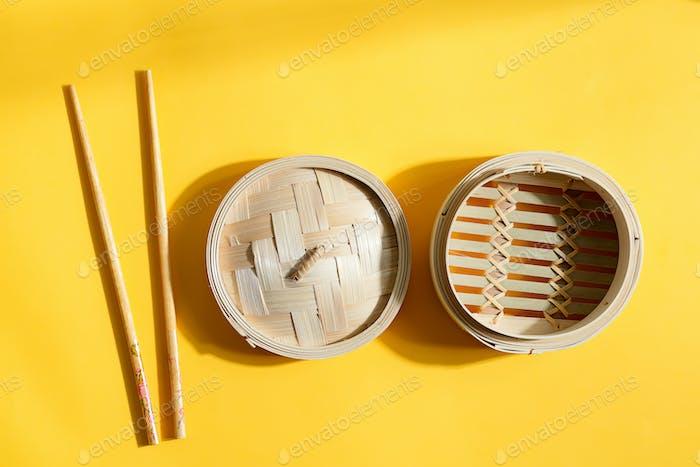 Asiatisches Küchenset Bambus Dampfgarer und Essstäbchen auf gelbem Hintergrund