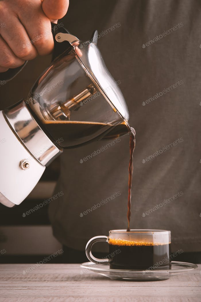 Man pouring coffee into a glass cup vertical