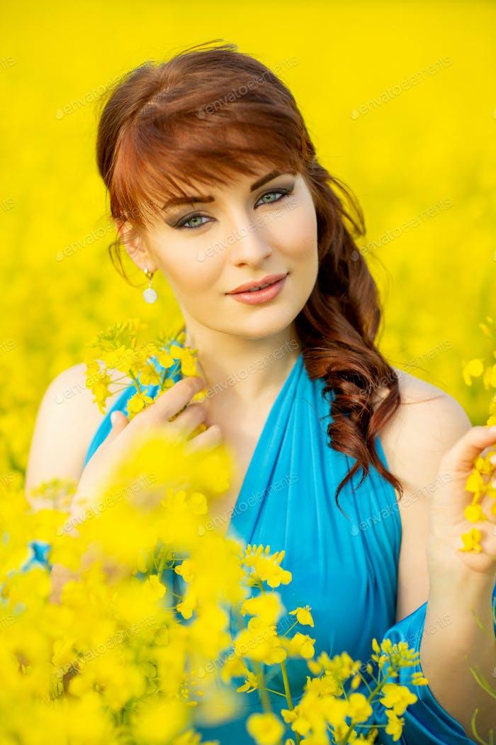 schönes Mädchen in blauem Kleid mit gelben Blumen