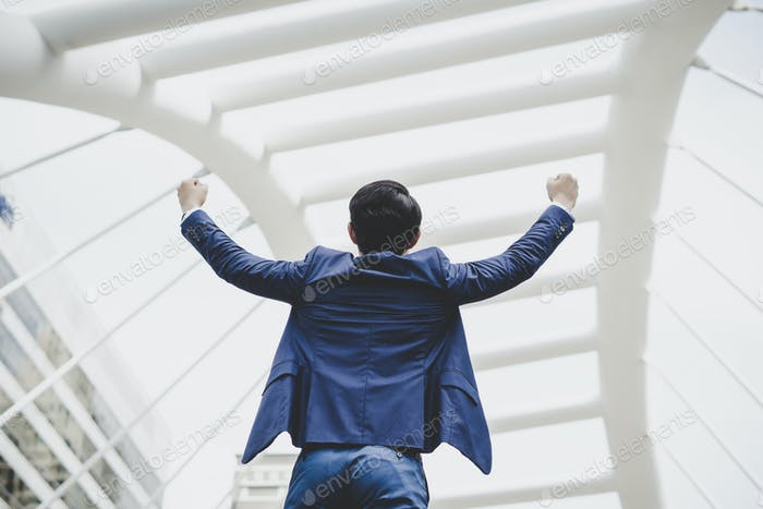 Successfully of young businessman keeping arms raised and expressing positivity while standing.