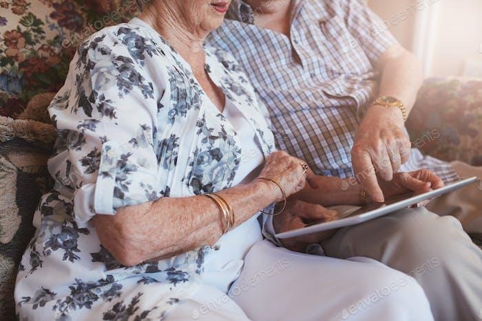 Старший пара сидит вместе с помощью компьютера с сенсорным экраном