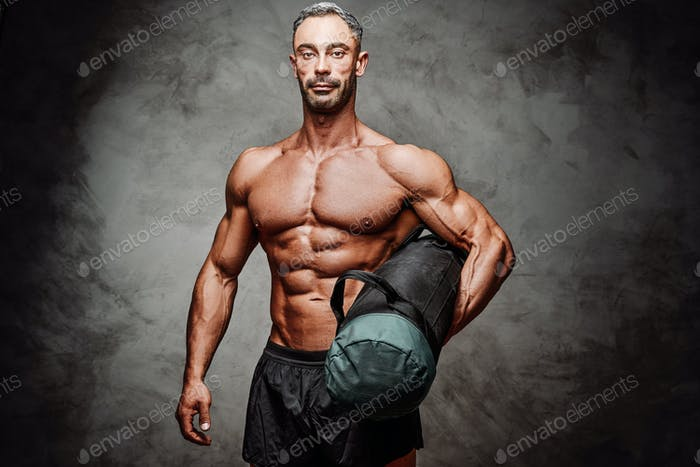 Embossed fitness couch posing in a studio with fitness gear