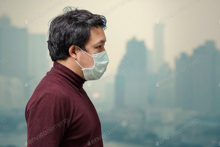 Asiatischer Mann trägt die Gesichtsmaske gegen Luftverschmutzung auf dem Balkon von High Apartment