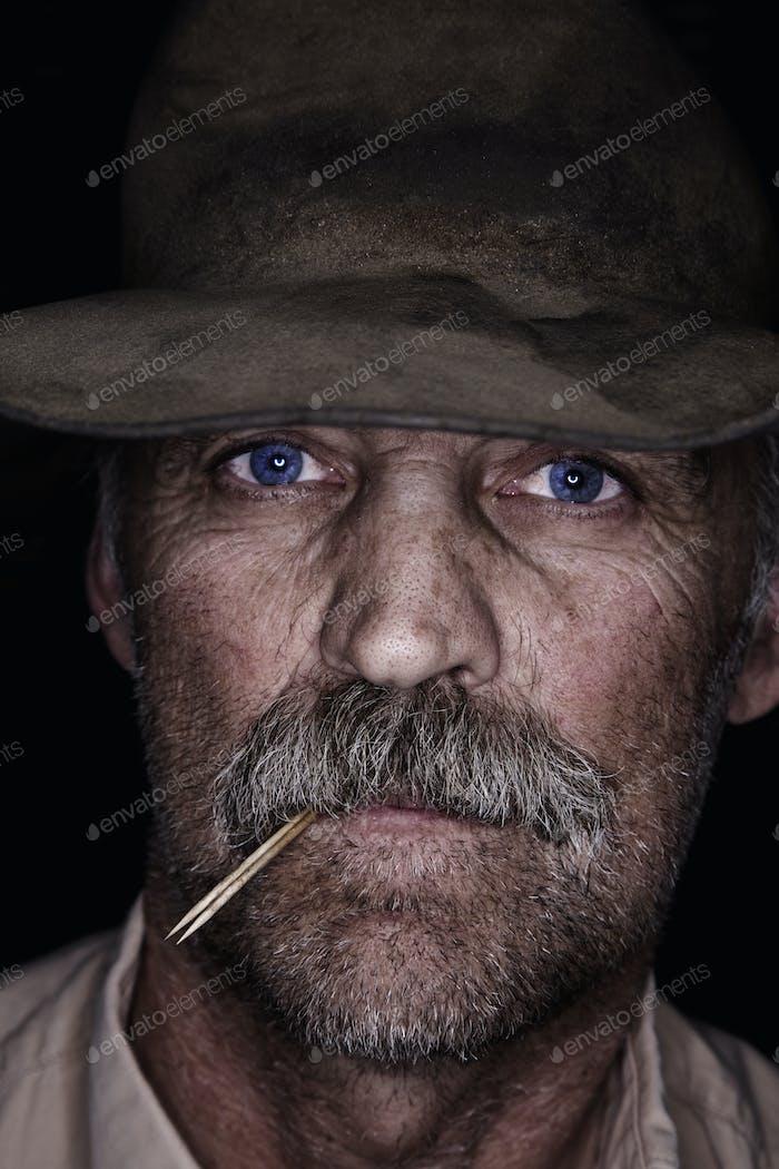 Ein Mann mit einem zerschlagenen Hut, mit blauen Augen und einem Schnurrbart, der ein Stück Stroh kaut. Ein Cowboy.