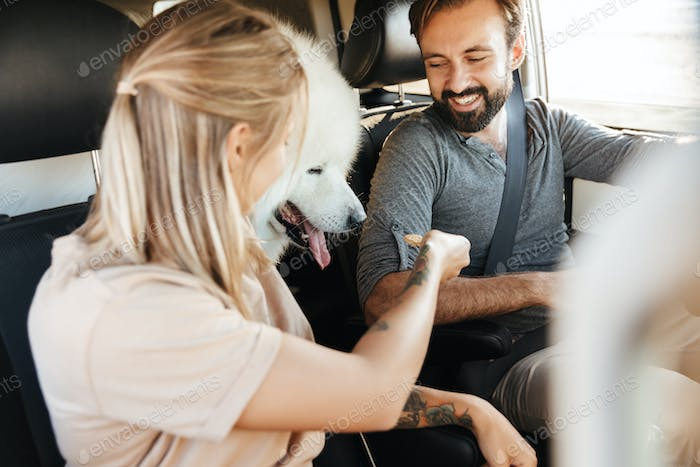 Cheerful young couple on a road trip with their dog