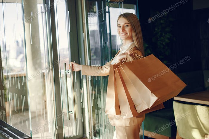 Stylish girl standing in a cafe with shopping bags