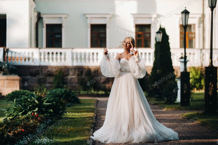 Beautiful bride in a luxurious wedding dress on a green natural background. Portrait of a happy
