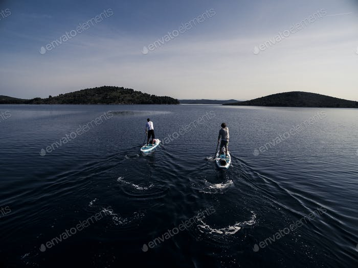 High angle shot of two people on paddleboards.