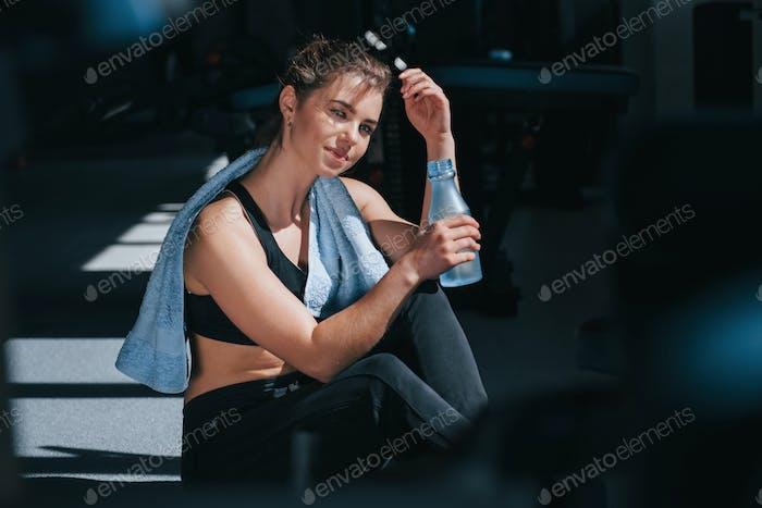 Limpieza por la toalla azul. Foto de hermosa rubia mujer en el gimnasio en su tiempo de fin de semana