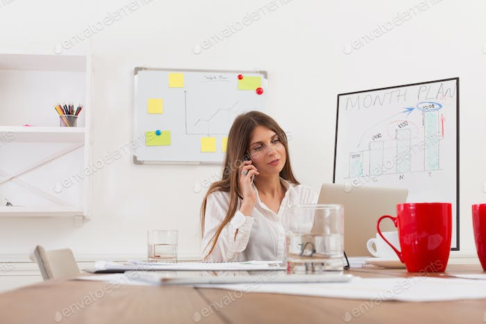 Beautiful young businesswoman sitting by office desk with laptop