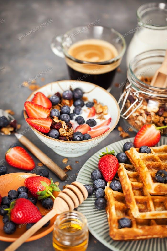 Frühstückstisch mit Müsli, Milch, frischen Beeren, Kaffee