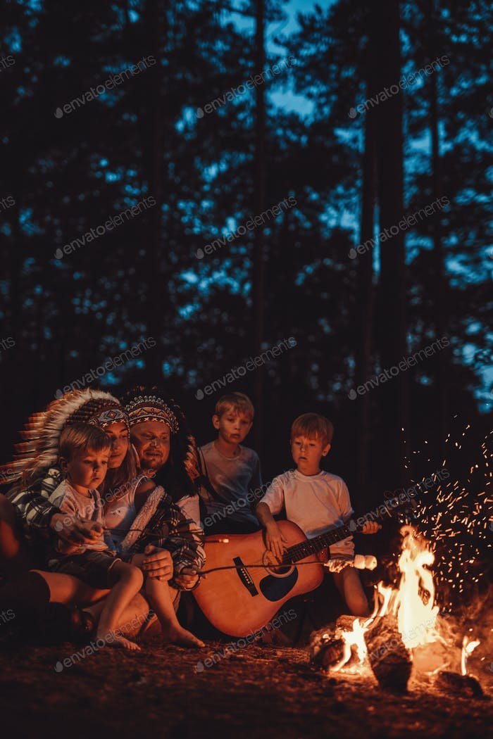 American family with indian headwear sitting near bonfire