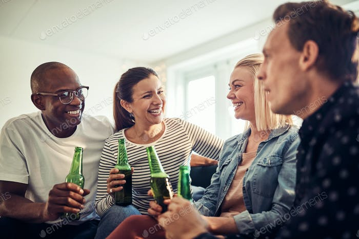 Laughing young businesspeople drinking beers together in an office