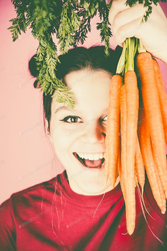 Teenager-Mädchen hält Bündel von frischen Karotten über rosa Hintergrund