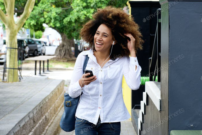 Young woman smiling with earphones and smart phone