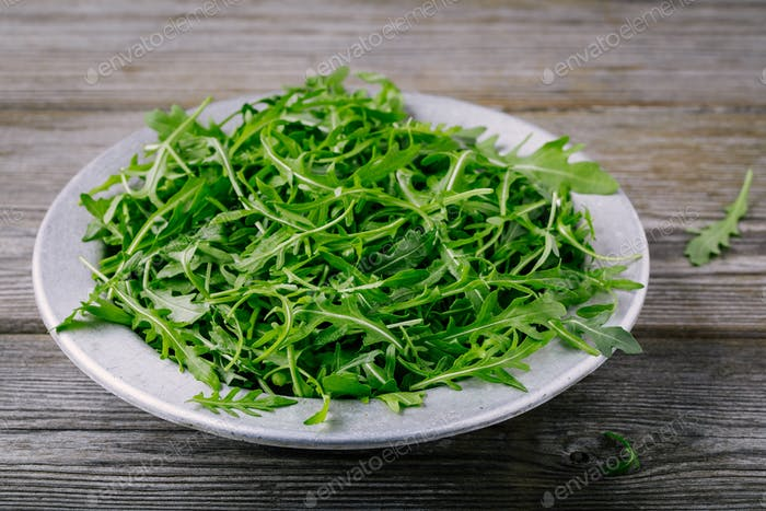 Fresh green arugula salad leaves in a bowl on a wooden background.