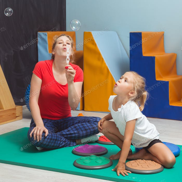 Child blowing bubbles during sensory integration therapy