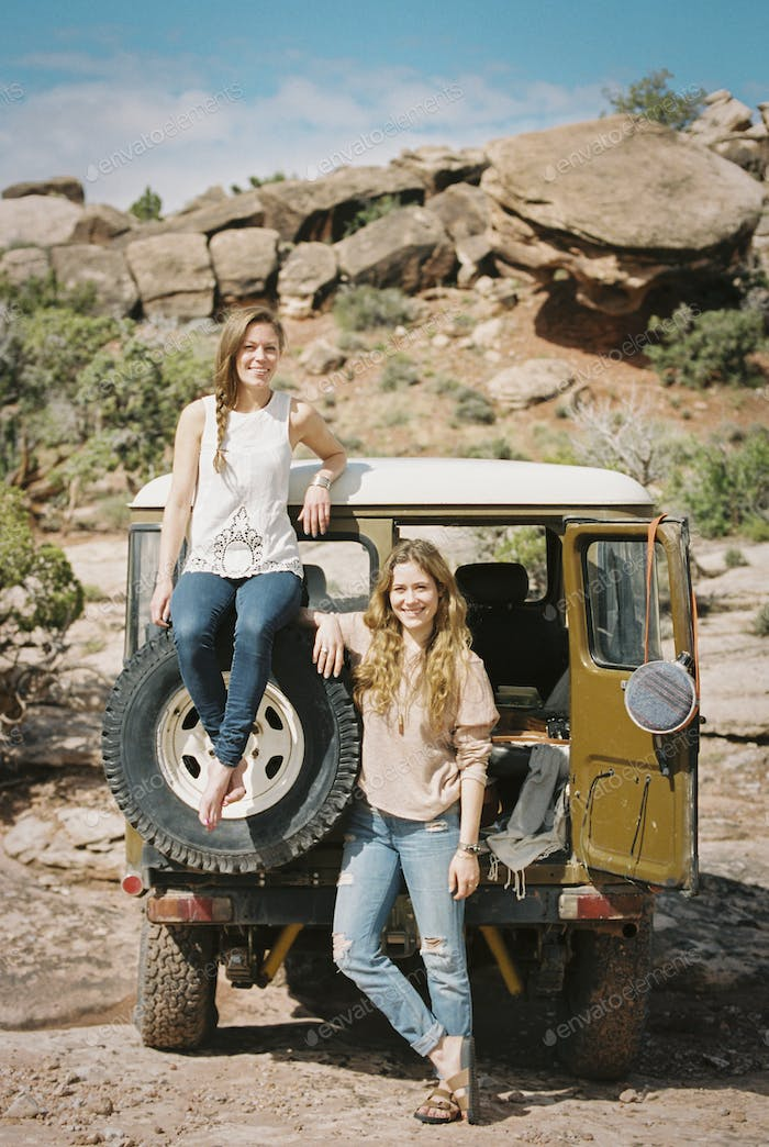Two women standing by a 4x4 on a mountain road.