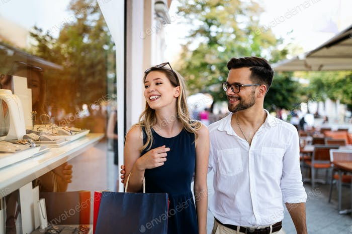 Couple of tourists shopping and walking in a city street