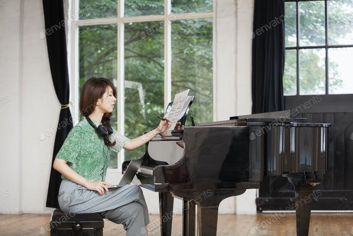 Young woman sitting at a grand piano in a rehearsal studio, annotating sheet music.