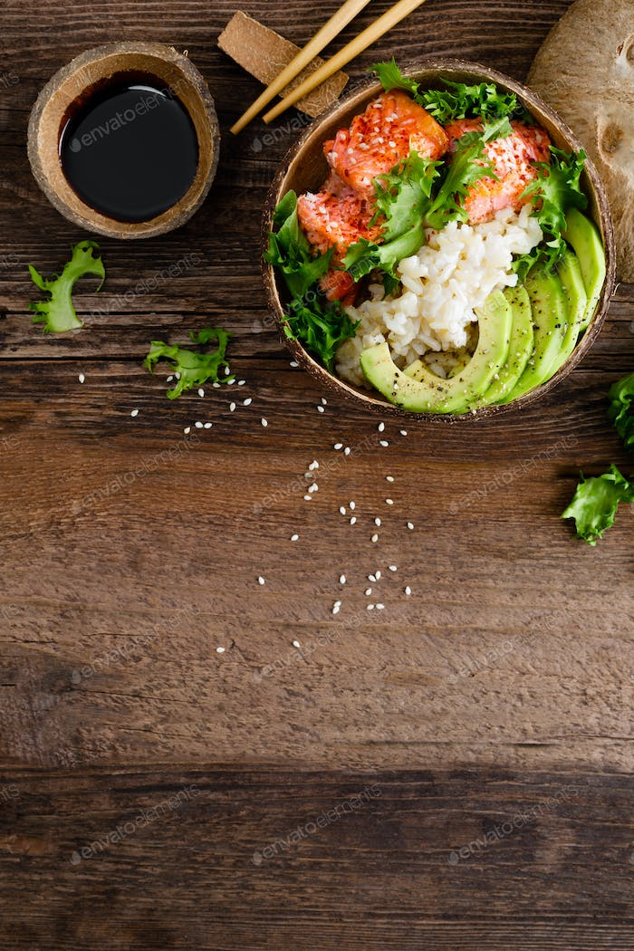 Hawaiian poke coconut bowl with grilled salmon fish, rice and avocado. Healthy food. Top view