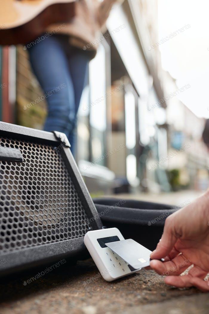 Nahaufnahme der person mit kontaktlosen zahlungsmaschine bei füßen der weiblichen musiker busking in street