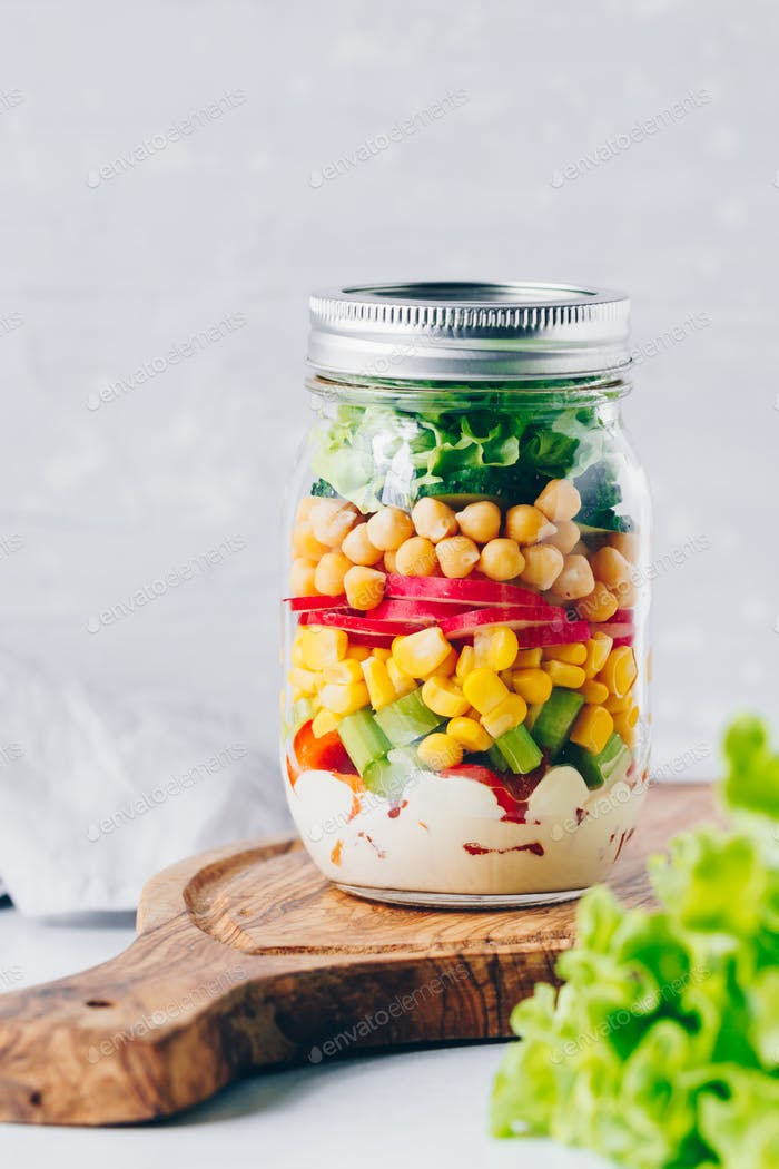 Layering vegetable salad in a glass jar.