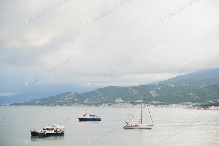 small tourist yachts and fishing boats without people in bad weather in bay