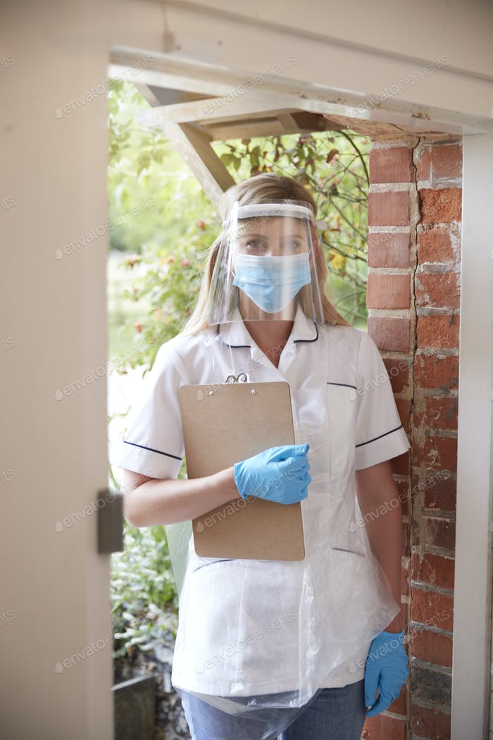 Portrait Of Female Health Worker Wearing Mask And Visor Visiting Patient At Home