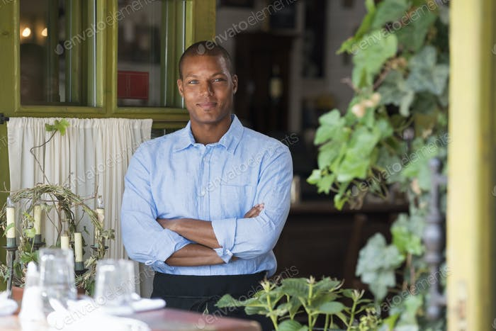 A man standing by the open window of a cafe or bistro, looking out with arms folded.