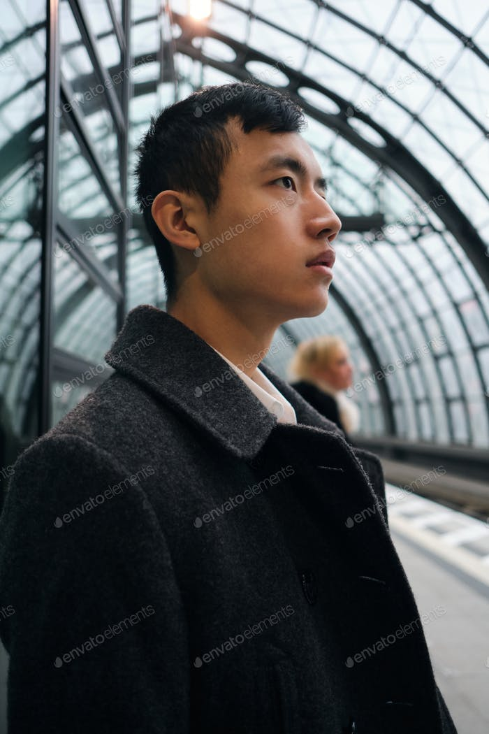 Side view of young Asian businessman thoughtfully waiting train at station