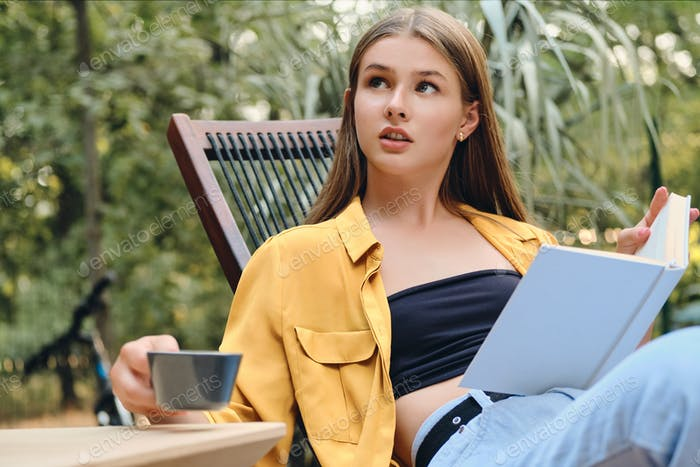 Teenage girl in yellow shirt thoughtfully sitting with book and cup of coffee in city park