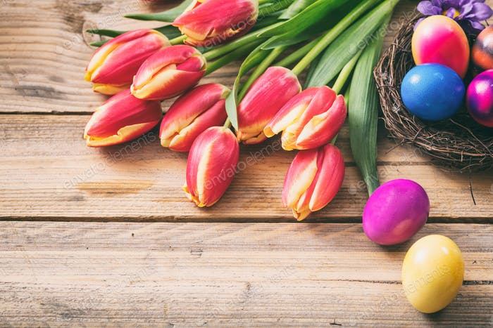 Easter eggs and fresh tulips on wooden background, copy space