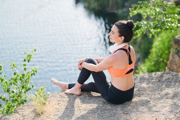 Content calm young woman in sportswear sitting on edge of quarry