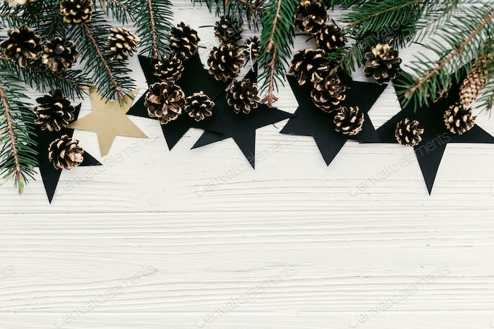Modern christmas layout with green fir branches, golden pine cones and stars