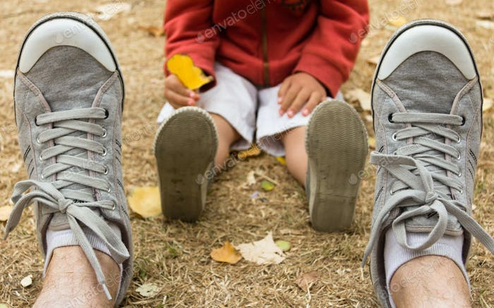 Sneakers front view of father sitting on field with his son