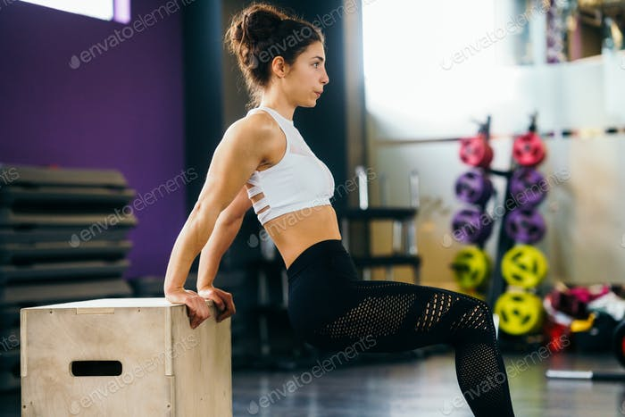 Athletic woman doing triceps push-ups at the gym