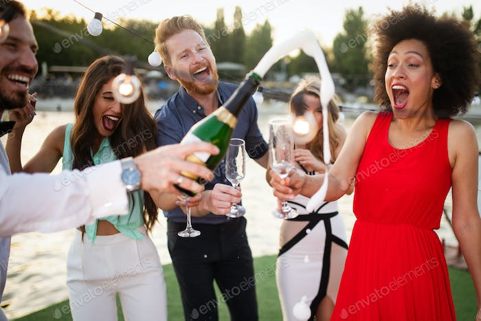 Group of happy people or friends having fun at party