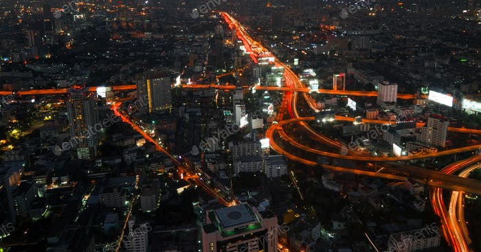 Futuristic night cityscape with traffic across street. Bangkok, Thailand
