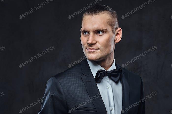 Портрет красивого стильного в элегантном классическая костюме с галстуком-бабочкой.