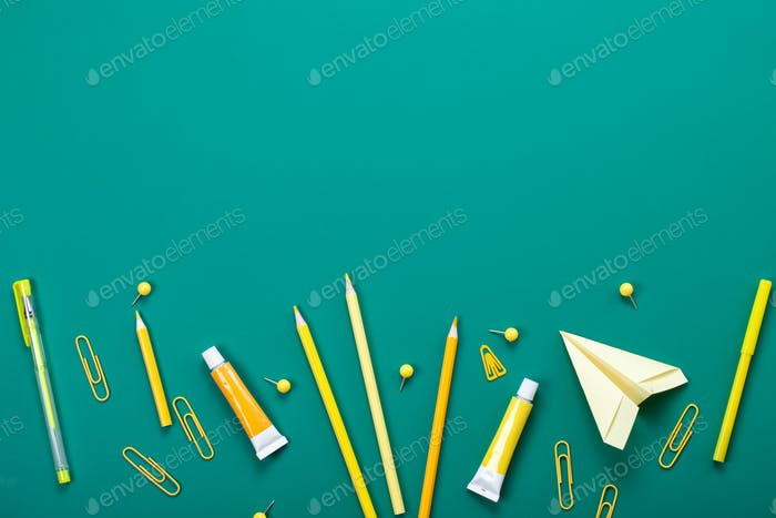 Yellow school supplies over the green board. Education, studing, back to school concept