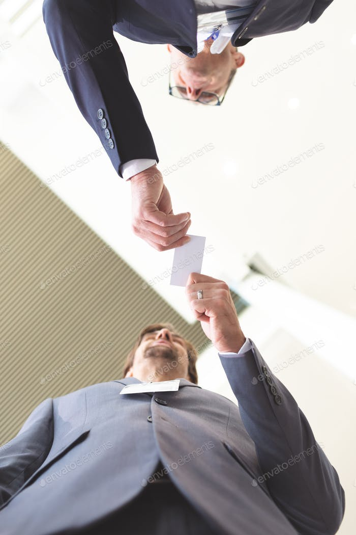 Upward view of diverse business people exchanging business card in conference