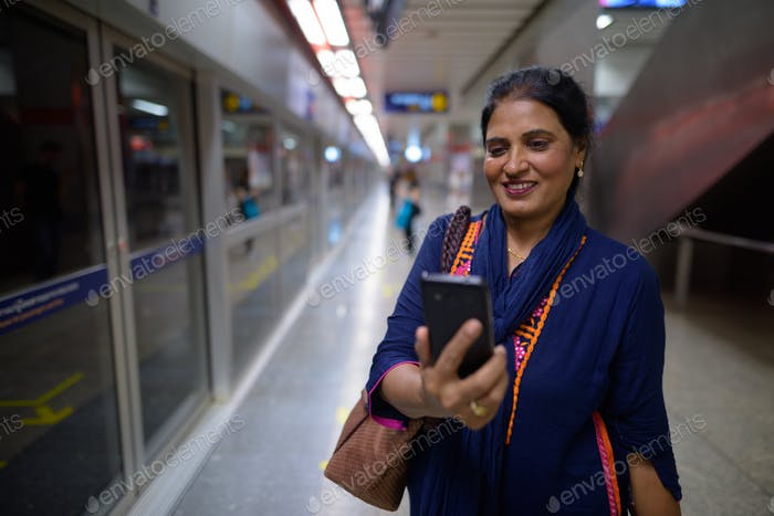 Indian woman using mobile phone at underground train station