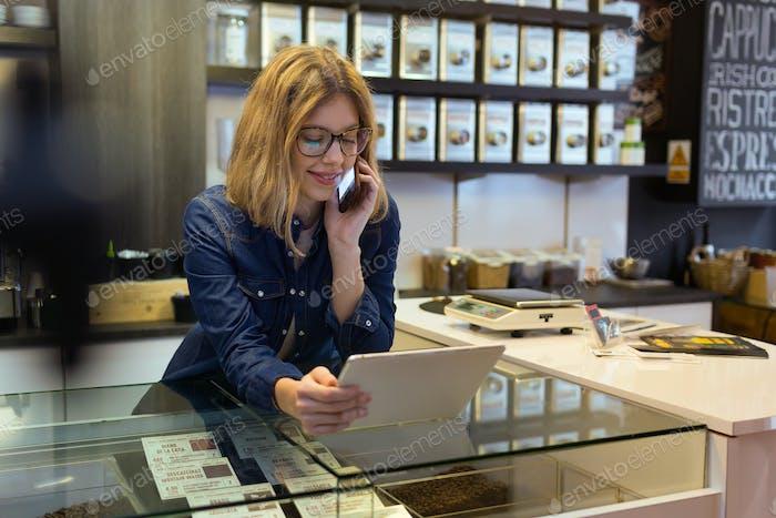 Schöne junge Verkäuferin mit ihrem digitalen Tablet in organischen s