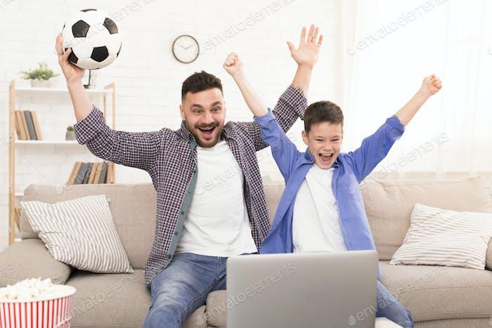Aufgeregt Vater und Sohn beobachten Fußball auf Laptop