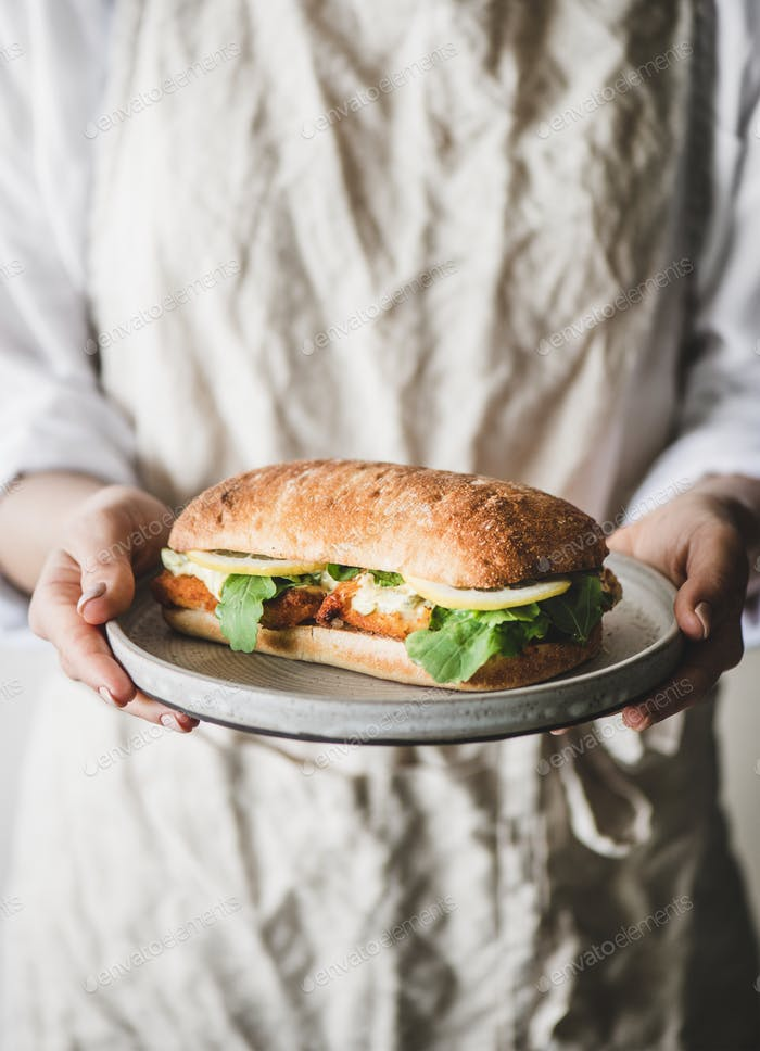 Frau in Leinen Schürze halten Frühstück Sandwich mit gebratenem Fisch