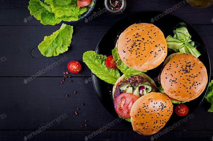 Big sandwich - hamburger burger with beef,  tomato,  cheese and lettuce. Top view. Flat lay