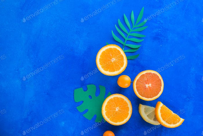 Exotic fruits close-up. Oranges, kumquats and other tropical fruits vibrant blue background with